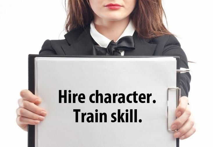 woman holding a sign that says Hire character, train skill